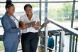 canvas print picture - Two beautiful African American businesswomen in bright modern of