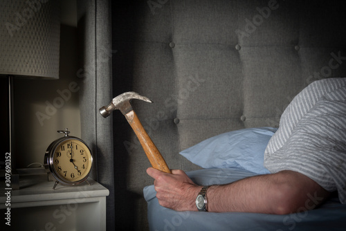 Person sleeping in bed about to strike their ringing morning alarm clock with a hammer Canvas Print