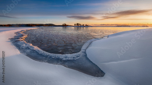 The first ice on the water in Lake Ladoga at dawn with fresh snow in winter Canvas-taulu