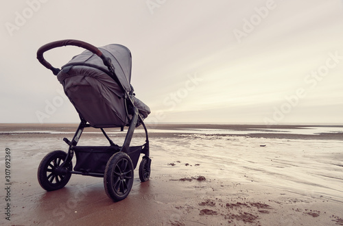 A infant baby childs stroller pushchair pram on a vast beach landscape at dusk and dawn Canvas Print