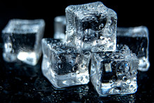 Ice Cubes / A Hill Of Transparent Ice Cubes On A Black Glass With Water Drops Around.