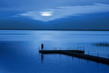 Man On Pontoon Pier In Blue Ni...
