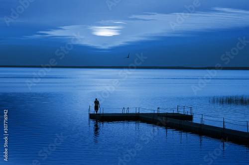 fototapeta na lodówkę Man on pontoon pier in blue night. Color of the year 2020 Classic Blue pantone