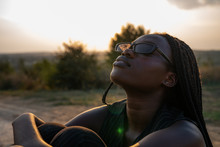 Young African Girl In Black Sunglasses Sits On The Dirt Road, Hugging Her Knees And Looking Up, Sunset On The Background