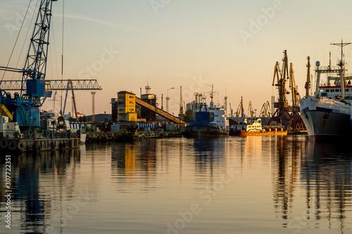 Fotografía  Russia, Kaliningrad, hoisting cranes in the commercial port at sunset
