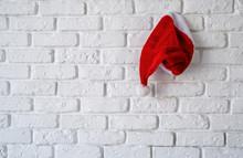 Red Santa Hat Hanging On White...