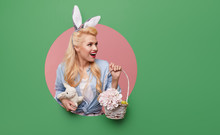Young Pin-up Woman With Easter Bunny Ears With A Basket Of Colored Eggs Crawls Out Through A Round Hole In The Wall. Menthol Or Turquoise Color Background. Holiday Card Blank