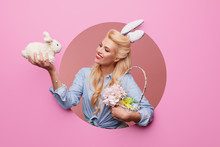 Happy Easter. Young Woman With Bunny Ears And Basket Full Of Easter Eggs On Pink Background. Crawls Out Through A Round Hole In The Wall.  Pin Up And Retro Style Fashion.
