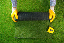 Men's Hands Hold A Roll Of Artificial Grass. Artificial Turf Background.