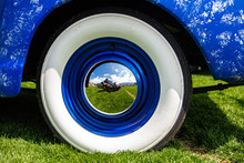 Vintage Classic American Bright Blue Car Wheels On The Grass, Close Up On The Steel Wheel Chrome Center With Reflection, And Whitewall Tire