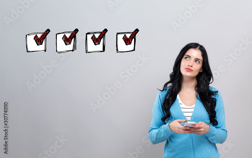 Checklist with thoughtful young woman holding a smartphone