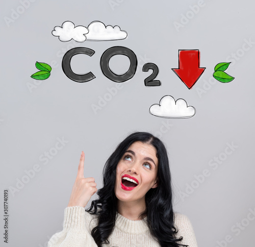 Reduce CO2 concept with happy young woman on a gray background