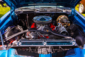 Blue classic muscle car, Open hood close up on red engine, Big chrome round air intake filter, tubes, wires, pipes, brake vacuum servo, other parts