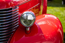 Old Vintage American Red Pickup Car Front Side Close Up View, With Chrome Glass Headlights Light Lamp Parts And Grille During An Outdoor Show