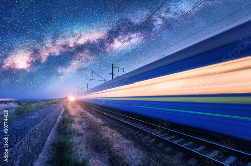 Fotomural  High speed train in motion and Milky Way at starry night