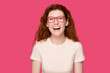 canvas print picture - Overjoyed millennial red-haired woman in eyeglasses head shot studio portrait.