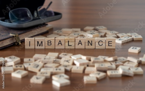Fotografie, Tablou  imbalance the word or concept represented by wooden letter tiles