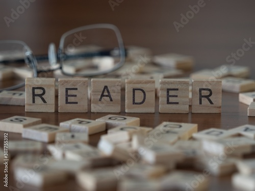 reader the word or concept represented by wooden letter tiles Fototapet