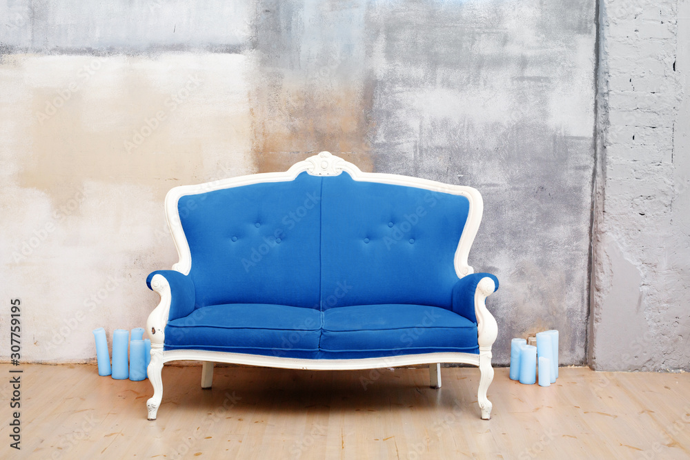 Fototapeta Elegant classic soft blue arm-chair near a concrete wall. Luxury interior with blue color in loft style. Armchair with fabric upholstery. Pontone of 2020 year