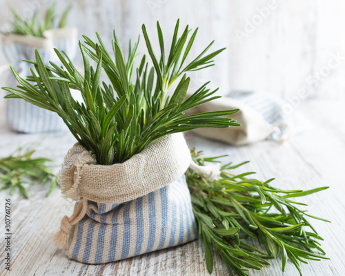 Carta da parati Fresh green rosemary in decorative linen bag on an old wooden table