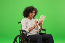 Happy Disabled Black Woman Using Tablet On Greenscreen