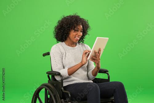 Obraz Happy disabled black woman using tablet on greenscreen - fototapety do salonu