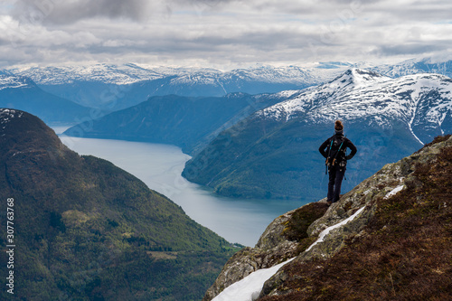 An explorer stands atop a mountain looking across a sweeping view of Norwegian f Wallpaper Mural
