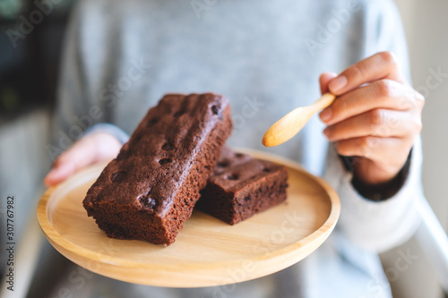 Closeup image of a woman eating delicious brownie cake with spoon