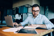 Content spectacled businessman working on startup project