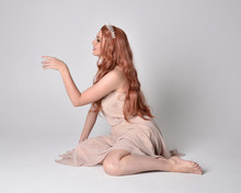 Full Length Portrait Of A Pretty, Fairy Girl Wearing A Nude Flowy Dress And Crystal Crown. Seated Pose Against A Grey Studio Background.