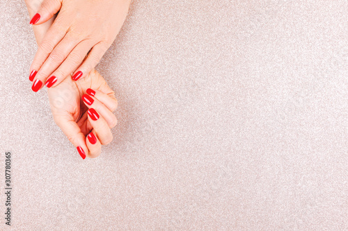 Woman hand with red manicure on glitter background. Holiday, party and celebration concept. Horizontal