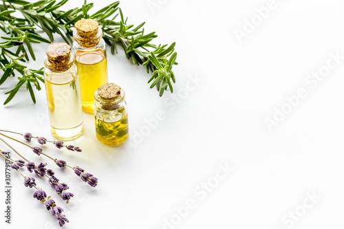 Fototapeta Aromatherapy. Essential oils in small bottles near fresh herbs on white background copy space obraz