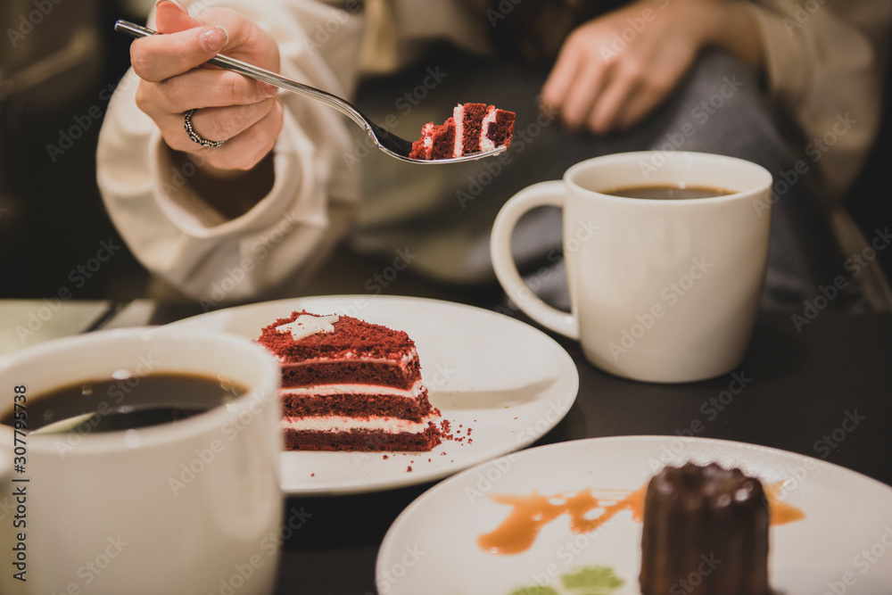 Fototapeta Close up of young woman having a relaxing time enjoying coffee and cake in a cafe