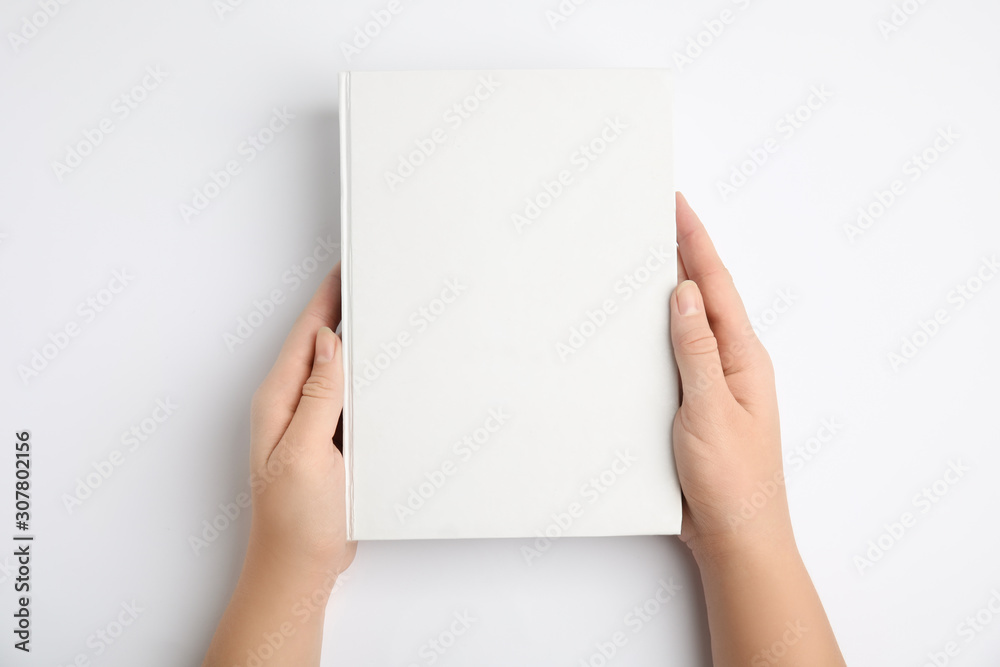 Fototapeta Woman holding book with blank cover on white background, top view