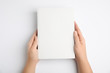 canvas print picture Woman holding book with blank cover on white background, top view