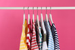 Leinwanddruck Bild - Colorful clothes hanging on rack against pink background