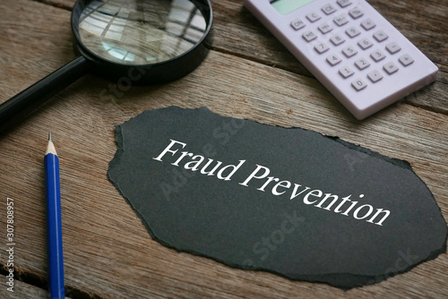 Fototapety, obrazy: Calculator,magnifying glass,pencil and piece of black paper written with Fraud Prevention on wooden background.