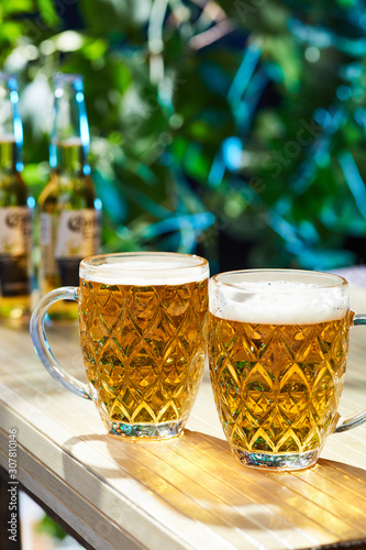 Valokuva Subject shot of dimple pattern beer mugs with frothy pale amber ale