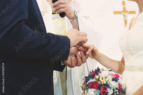 Nowożeńcy nakładają obrączki podczas wypowiadania słów przysięgi małżeńskiej Wallpaper Mural