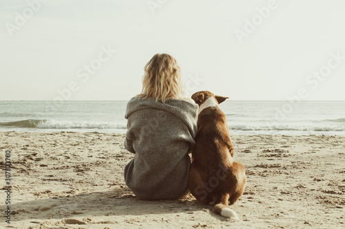 Photo Young woman sitting and hugging dog on the beach