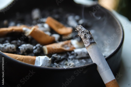 one burning cigarette placed on ashtray full of smoked cigarettes, extreme close Wallpaper Mural