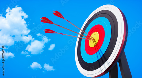 Leinwand Poster Colored target board with arrows in the sun against blue sky with small clouds -