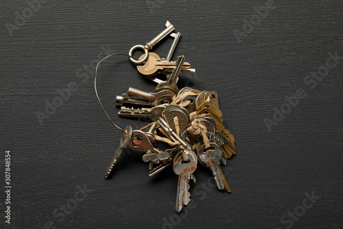 Fototapeta top view of vintage rusty keys in bunch on black background obraz