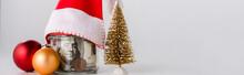 Panoramic Shot Of Christmas Balls And Jar With Dollar Banknotes And Santa Hat On White