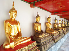 Golden Buddha Statues Sitting In A Meditative Pose, In A Temple Complex With Marble Floors And A Red Traditional Ceiling In Bangkok In Thailand