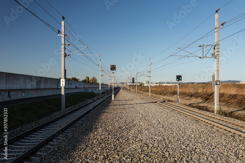 Obraz na plátne Two train tracks receding into the distance in a suburban area of a large europe