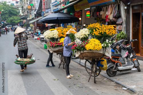 Fototapeta Flower vendor on Hanoi old town street at early morning obraz na płótnie