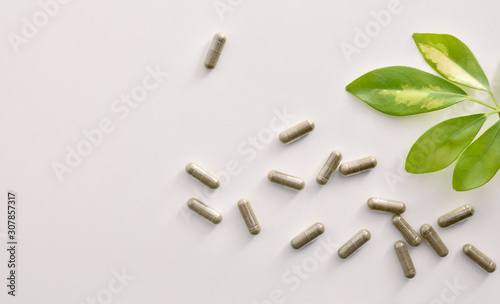 Background with capsules and plant on white table top view Obraz na płótnie