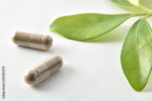 Carta da parati Two natural medicine capsules and plant on white table detail