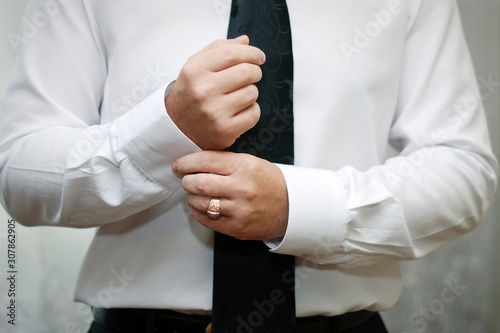 A man fastens with a cufflink on the cuff of the sleeve of a luxurious white shirt Wallpaper Mural